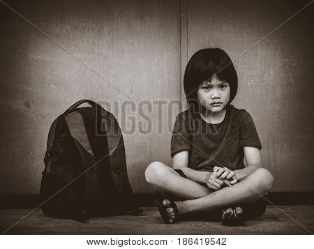 Retro picture with grain. Sad Kid sitting on the floor with school bag waiting for parent.