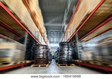 Warehouse industrial and logistics companies. Coiled plastic pipe. Motion blur effect.