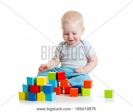 Kid boy building from toy blocks. Isolated on white background