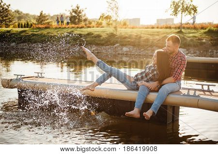 Happy couple walking in the park dressed in a plaid shirt. They sit on the pier and do splashes with their feet