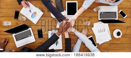 Multiethnic Team put hands together, connection, teambuilding and alliance concept. People in the office top view