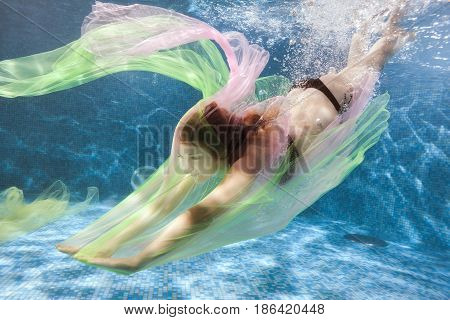 Woman swims in the pool and plays with a colored cloth she's a scuba diver.