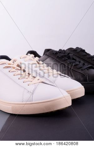 Two Pair Of Sneakers Shoes On Black Background. Black And White Shoe.