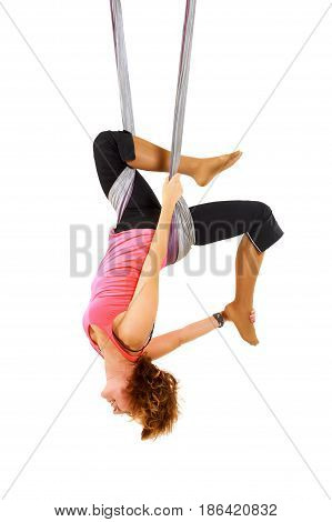 Young woman doing aerial yoga. Isolated on white.