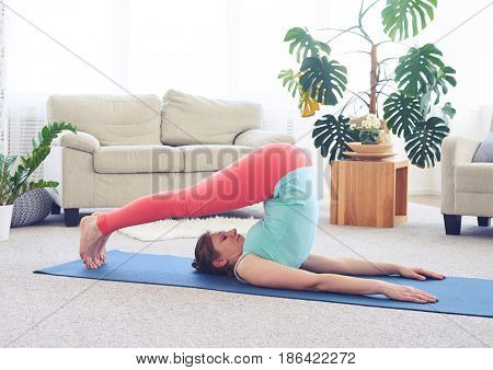 Wide shot of good-looking lady in plow asana on yoga mat