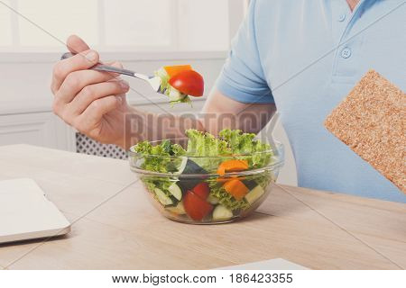 Healthy eating, business lunch in modern office. Unrecognizable man cropped image, businessman in t-shirt at working place eating salad