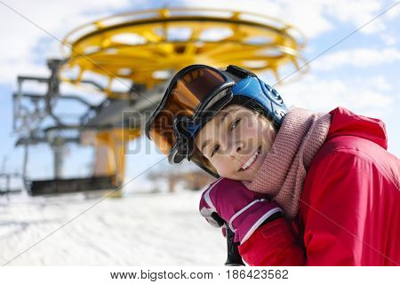 Girl with ski goggles smiles near modern funicular in ski resort at winter day