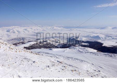 Beautiful mountains in snow in ski resort, power plant, Sevan lake far away, Tsakhkadzor, Armenia in winter sunny day