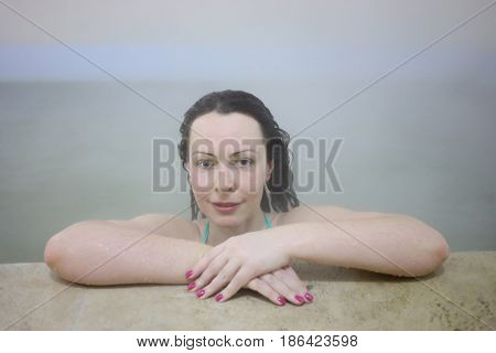 Happy beautiful woman rests in warm thermal source among steam