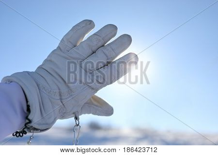 Hand in glove - skier hides sun by palm on mountain in snow at winter