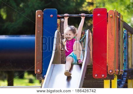 Child Playing On Outdoor Playground In Summer