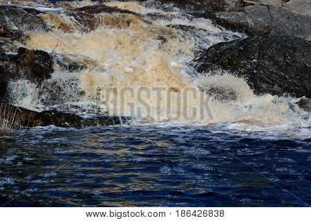 The turbulent waterfall flows over the rocks. Nature of water wild places.