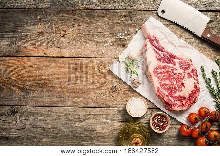 Raw tomahawk beef steak with ingredients for grilling: seasoning, fresh rosemary and olive oil on wooden background, top view