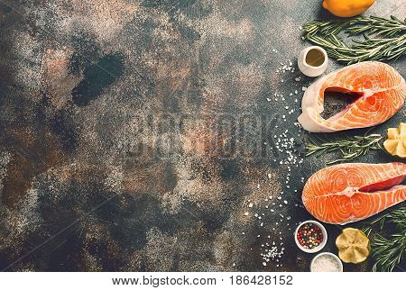 Fresh raw salmon steak, lemon, rosemary and spices on dark rustic concrete background. Food frame top view with copy space. Ingredients set for making healthy dinner. diet concept.