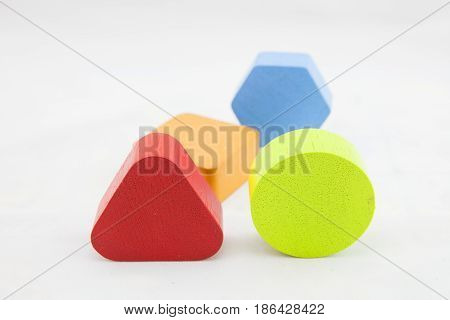 The concept of logical thinking. Colorful wooden blocks on white background. Geometric shapes - cube, triangular prism, cylinder on white background. The concept of logical thinking.