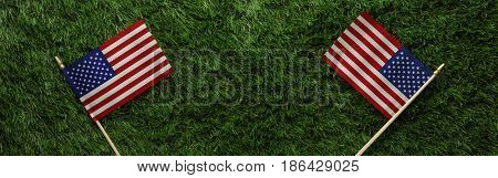 Red, white, and blue American flags on grass for Memorial Day or Veteran's day background