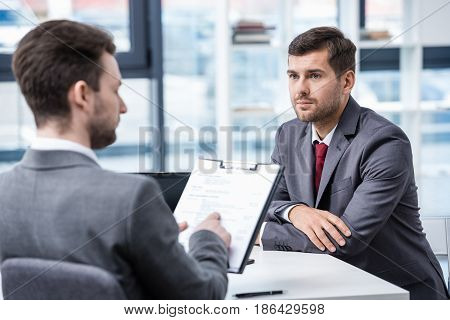 Serious Man In Formal Wear Looking At Businessman With Clipboard During Job Interview, Business Conc