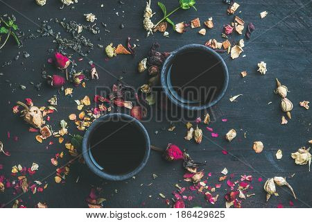 Chinese black tea in black stoneware cups over black wooden background with herbs, flower buds, tea leaves spilt around, top view