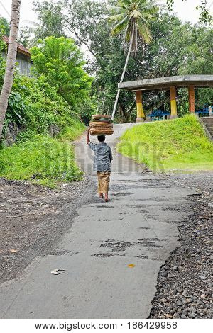 Balinese man in traditional clothes carrying household goods on his head in Bali Indonesia