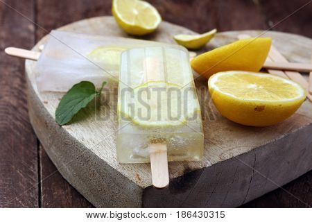 Healthy Lemon Popsicles With Fresh Lime Slices On Wooden Background