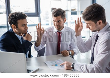 Young Businessmen In Formal Wear Discussing Business Charts And Showing Ok Sign, Business Concept