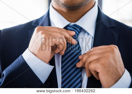 Partial View Of Elegant Businessman In Suit Tying Necktie