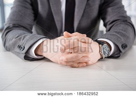 Partial View Of Businessman With Hands In Lock Sitting At Table, Business Concept