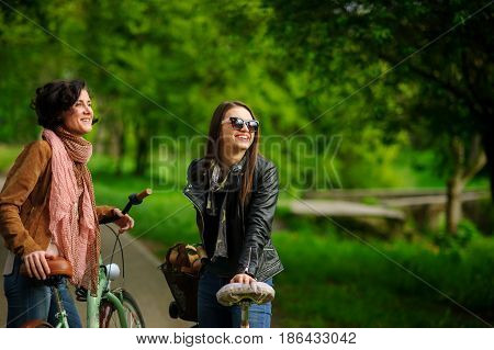 Two young attractive women ride bikes in the spring park. Pleasure by nature and movements. Healthy lifestyle.