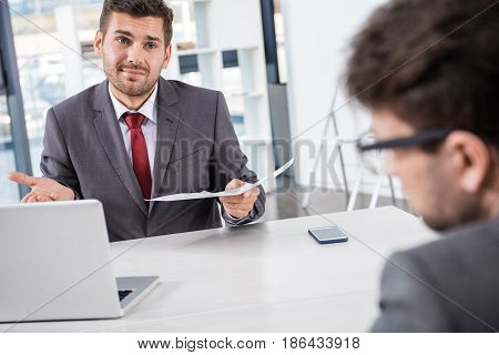 Unsatisfied Boss With Documents Looking At Colleague At Business Meeting