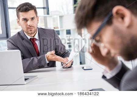 Unsatisfied Boss Looking At Upset Colleague At Business Meeting