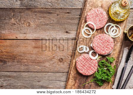 Raw meat burgers with onion and spices on rustic wooden background, top view