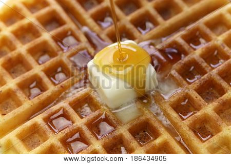 pouring maple syrup over homemade american round waffles with butter