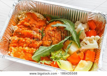 Healthy food, diet concept. Lunch box with Weight loss nutrition closeup. Couscous with topmatop sauce and vegetables