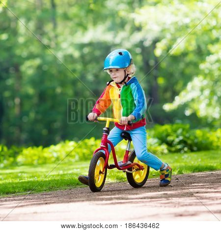 Child riding balance bike. Kids on bicycle in sunny park. Little boy enjoying to ride glider bike on warm summer day. Preschooler learning to balance on run bicycle in safe helmet. Sport for kids.