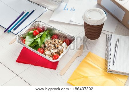 Healthy lunch box in office, coffee take away cup and vegetable salad in foil container on white wooden desk. Snack at break time