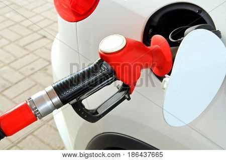 Gas pump in the car. White car refueling on a petrol station. Gasoline pump refueling. Car at the petrol gas station. close-up view.