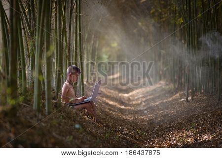 Local boy playing notebook on bamboo forest background.