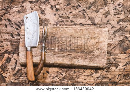 Vintage Meat cleaver, fork and cutting board on old wooden background