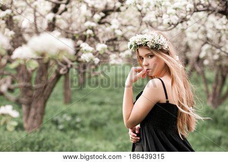 Beautiful blonde teen girl 14-16 year old posing in orchard. Looking at camera. Summer season.