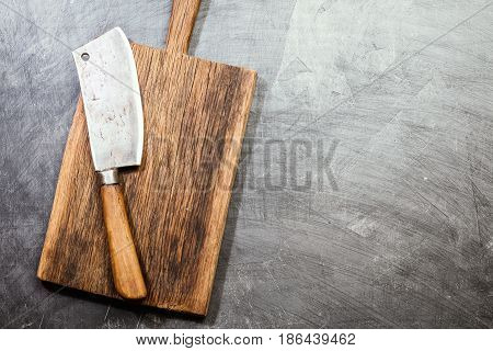 Vintage Meat cleaver and cutting board on chalk board background