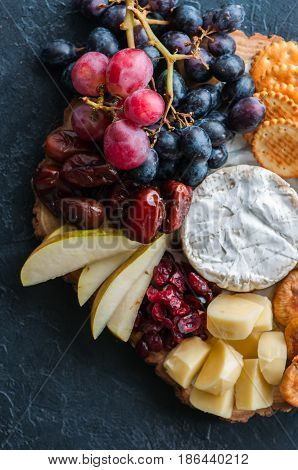Cheese Plate Grape Salted Cracker Cookies Dry Dates Cranberry, Fig, Pear Pretzels On A Wooden Board