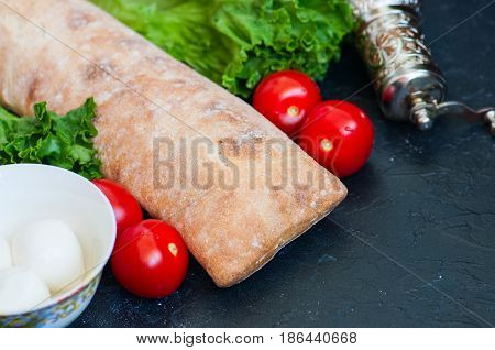 Freshly baked ciabatta bread with cherry tomatoes mozzarella lettuce salad leaf on a black slate background