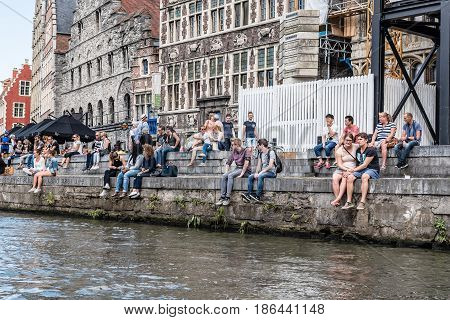 Ghent Belgium - July 31 2016: A crowd of students sitting on riverside of Embankment Graslei in the historic center of Ghent