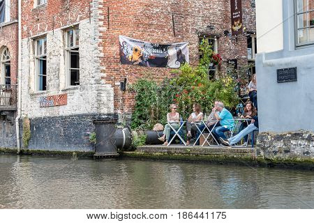 Ghent Belgium - July 31 2016: People sitting on a restaurant terrace in Embankment Graslei in the historic center of Ghent with picturesque old buildings