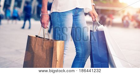 Detail of a woman holding shopping bags. Sun flare effect