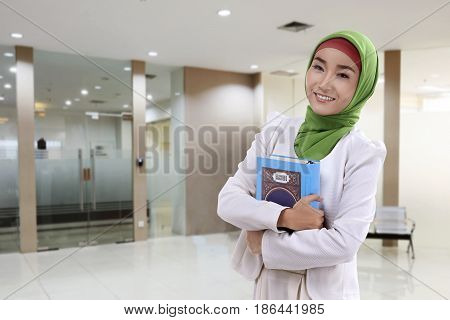 Young Asian Muslim Woman In Veil With Koran Standing