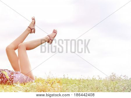 Low section of woman with feet up lying on grass against sky