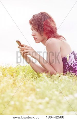 Side view of young woman text messaging through cell phone while lying on grass against clear sky
