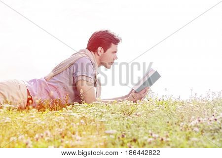 Side view of young man reading book while lying on grass against clear sky