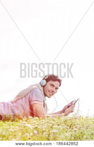 Side view portrait of man listening to music on MP3 player using headphones in park against clear sky